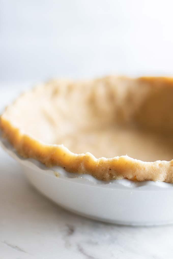 A flakey almond flour pie crust pressed into a white pie plate.