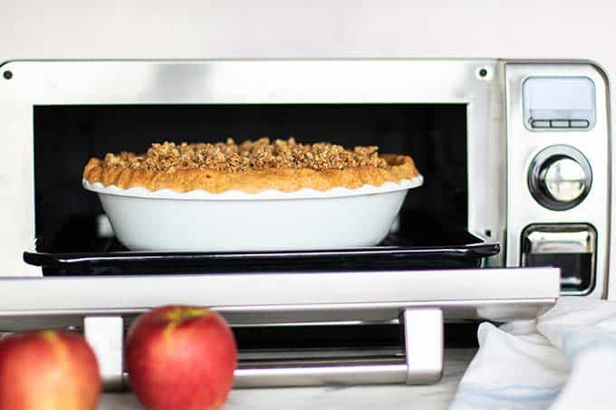 A baked gluten free apple pie being taken from the oven.