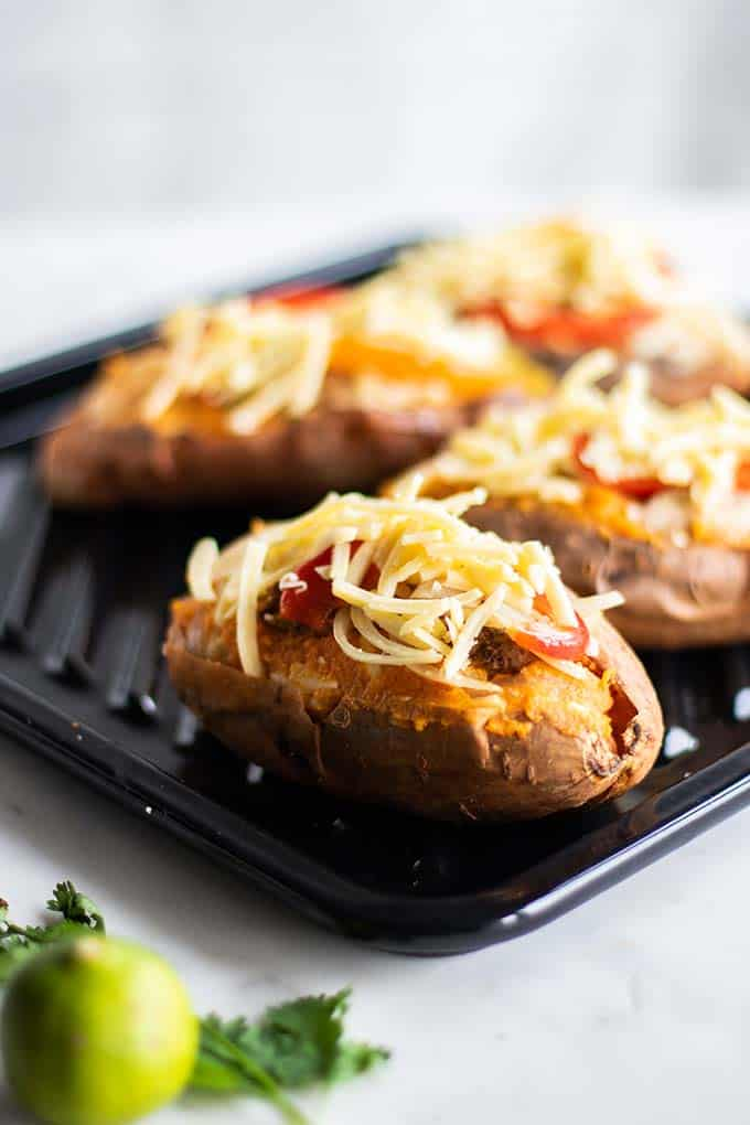 Baked sweet potatoes stuffed and topped with cheese, ready to be baked a second time.