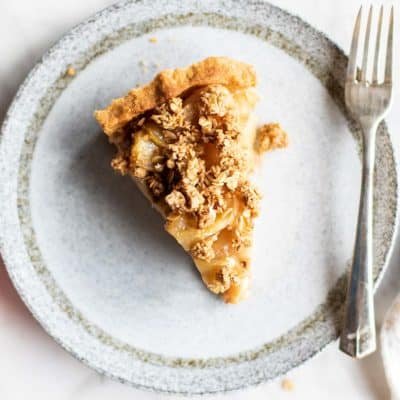 A healthy apple pie with a gluten free pie crust shown sliced on a plate.