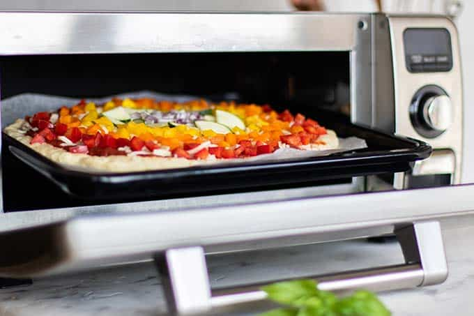 Putting a topped paleo pizza crust into the Sharp Superheated Steam Countertop Oven.