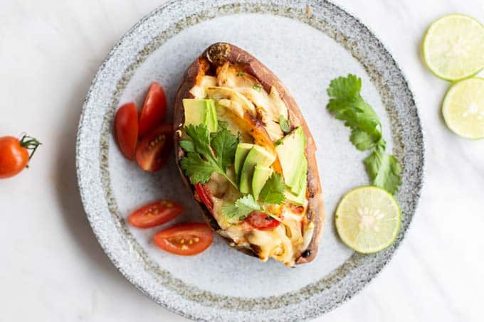 A chicken fajita stuffed sweet potato shown on a plate.