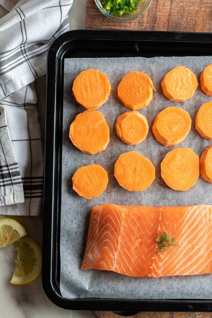 Sliced sweet potatoes and salmon on a baking tray.