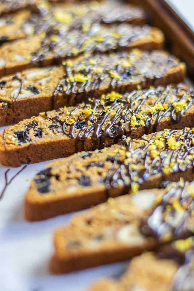 A tray of biscotti being drizzled with dark chocolate and sprinkled with orange zest.