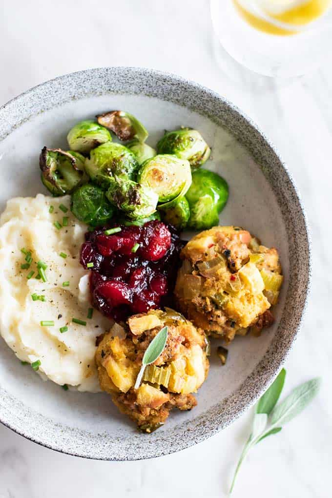 Two sausage stuffing balls on a plate with cauliflower mash and brussels sprouts.
