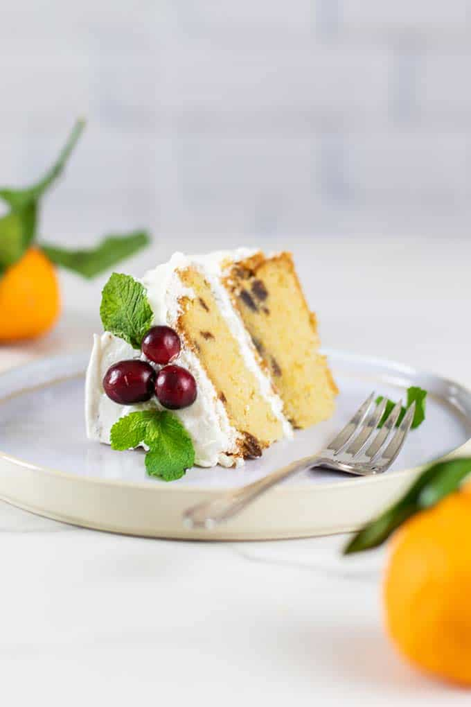 A slice of almond flour cake decorated with cranberries and mint.