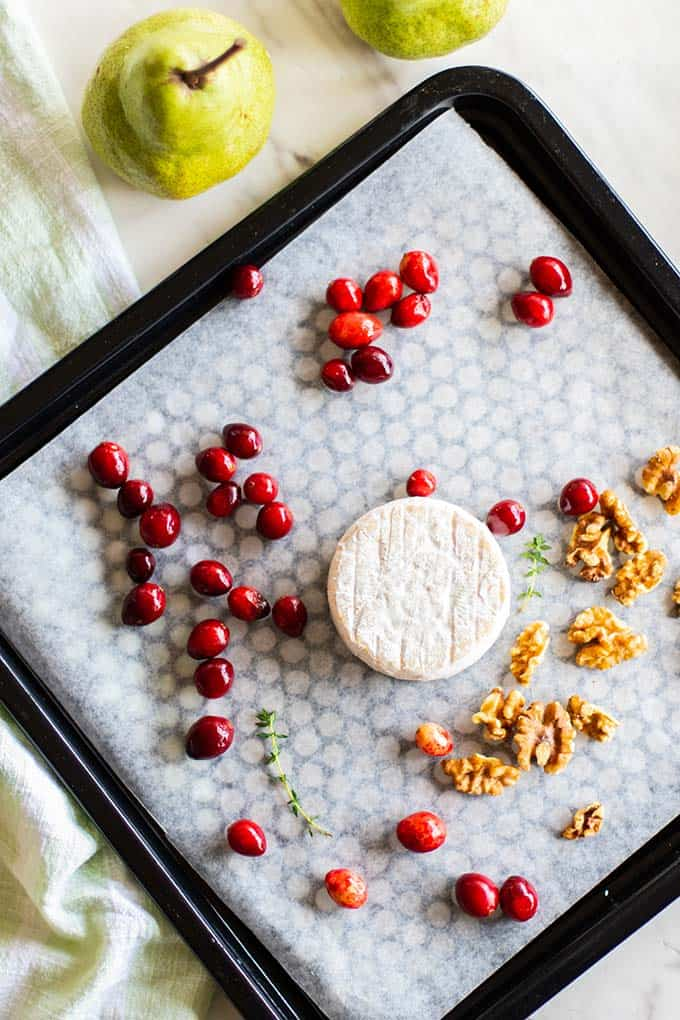 Brie, cranberries and walnuts on a baking tray.