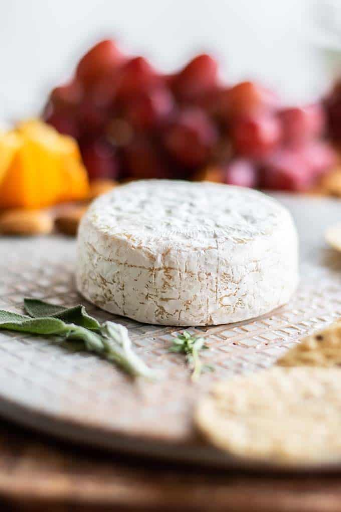 Brie on a cheeseboard before it's topped with chutney.