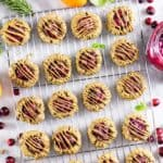 Baked cranberry breakfast cookies drizzled with sunflower seed butter cooling on a rack.