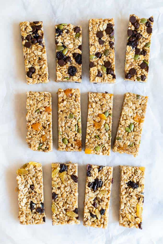 Three different flavors of granola bars sliced and laying on a piece of parchment paper.