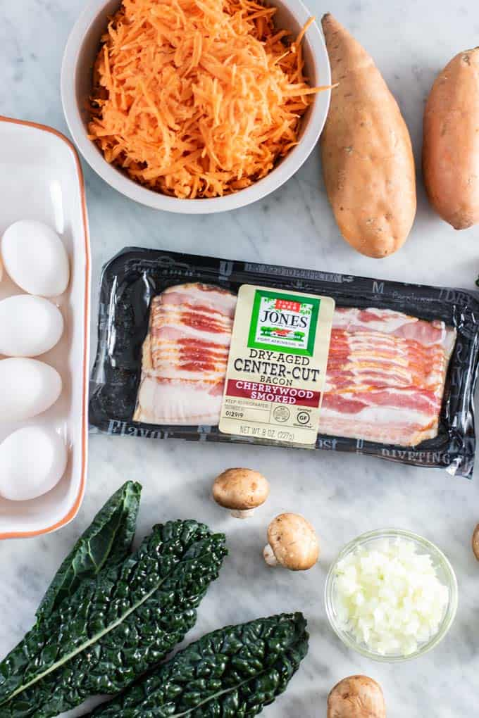 Jones Dairy Farm Bacon shown with shredded sweet potatoes, eggs, kale and mushrooms.