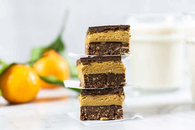 Three Nanaimo bars stacked in front of a glass of milk.