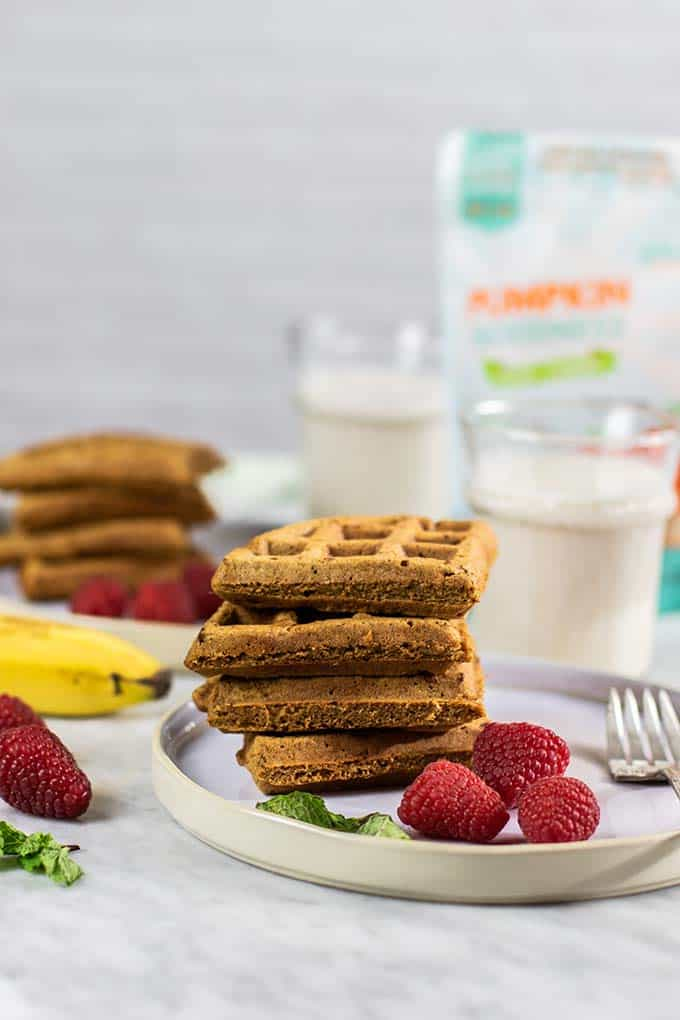 Stacks of pumpkin gluten free waffles with bags of vegetable flours.