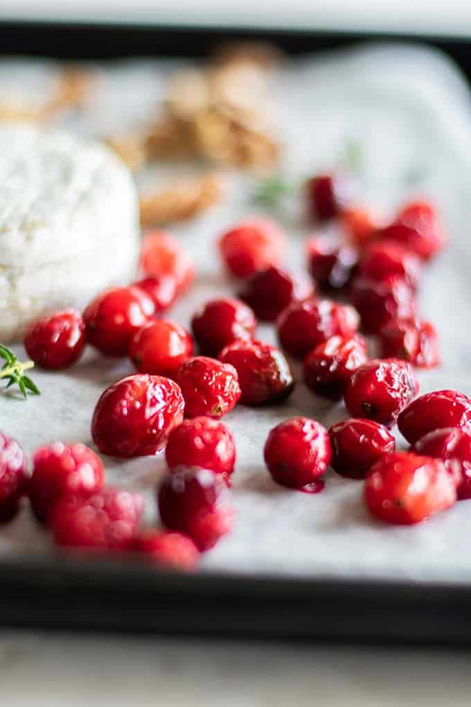 Cranberries roasted on a baking tray next to baked brie.