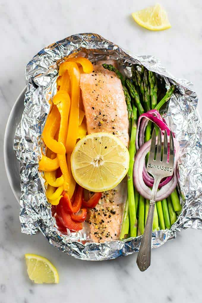 A foil packet with lemon pepper seasoned salmon and colorful vegetables.