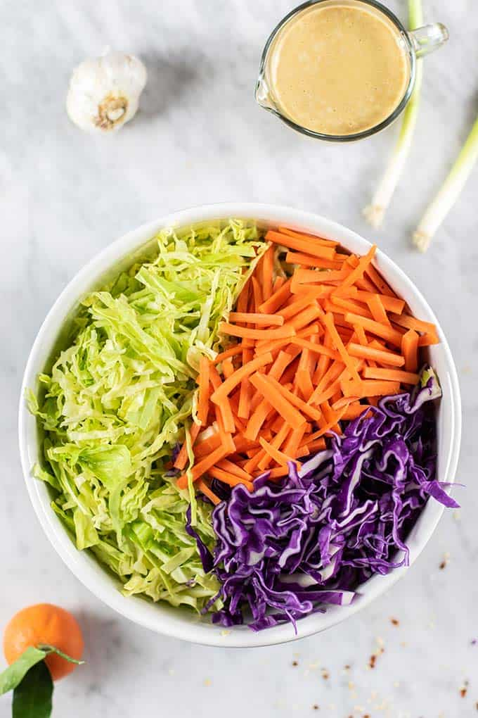 A bowl filled with cabbage and carrots, with a container of dressing on the side.