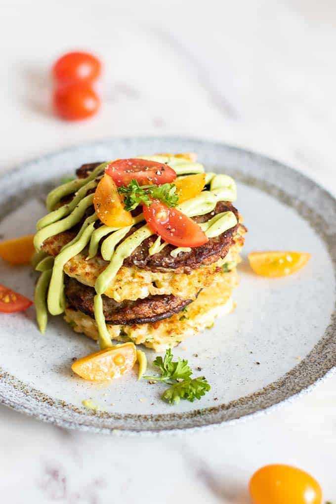 Cauliflower fritter and sausage stacks drizzled with avocado sauce and served with tomatoes.