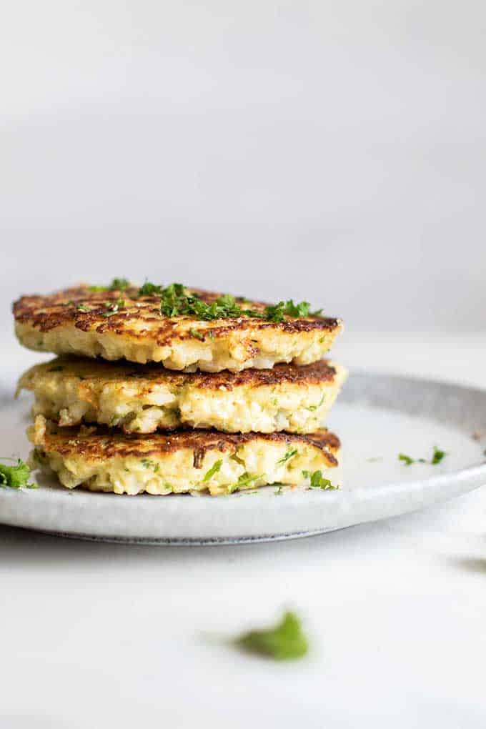 A stack of golden brown paleo cauliflower fritters.