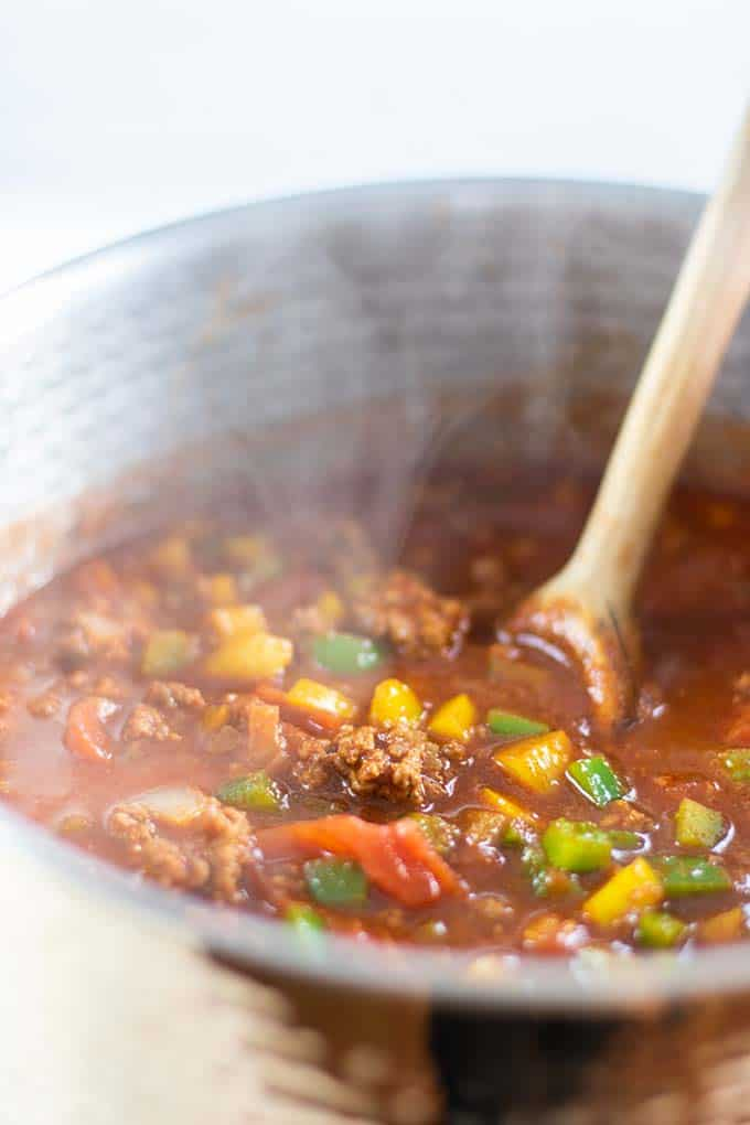 A steamy pot of chili, adding ingredients.
