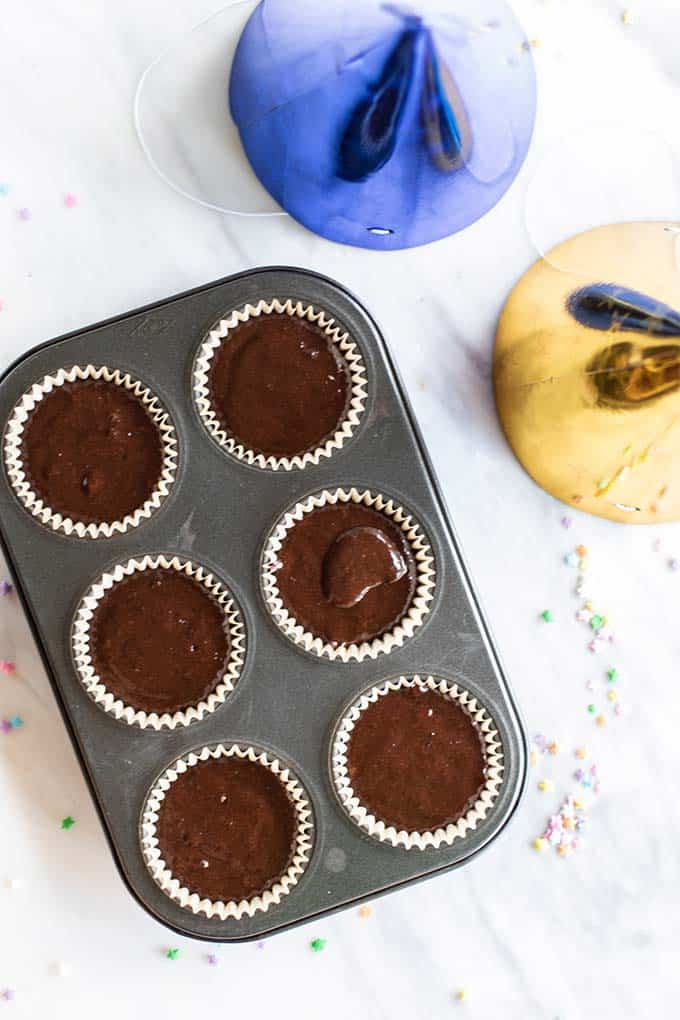 A muffin tin shown with gluten free cupcake batter.