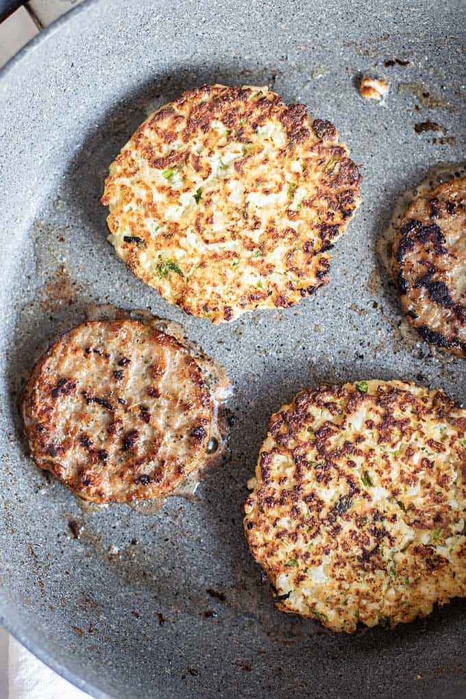 A pan showing frying caulfilower fritters and sausage patties.
