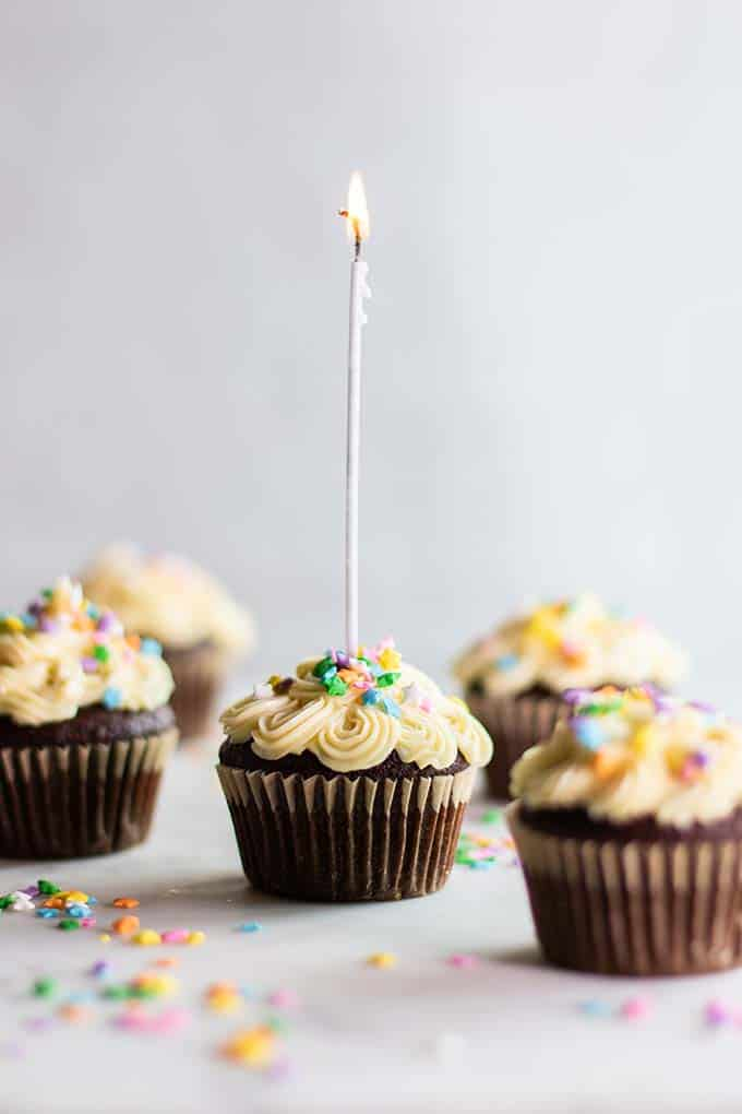 Gluten Free chocolate cupcakes decorated with white buttercream frosting and little colored sprinkles.