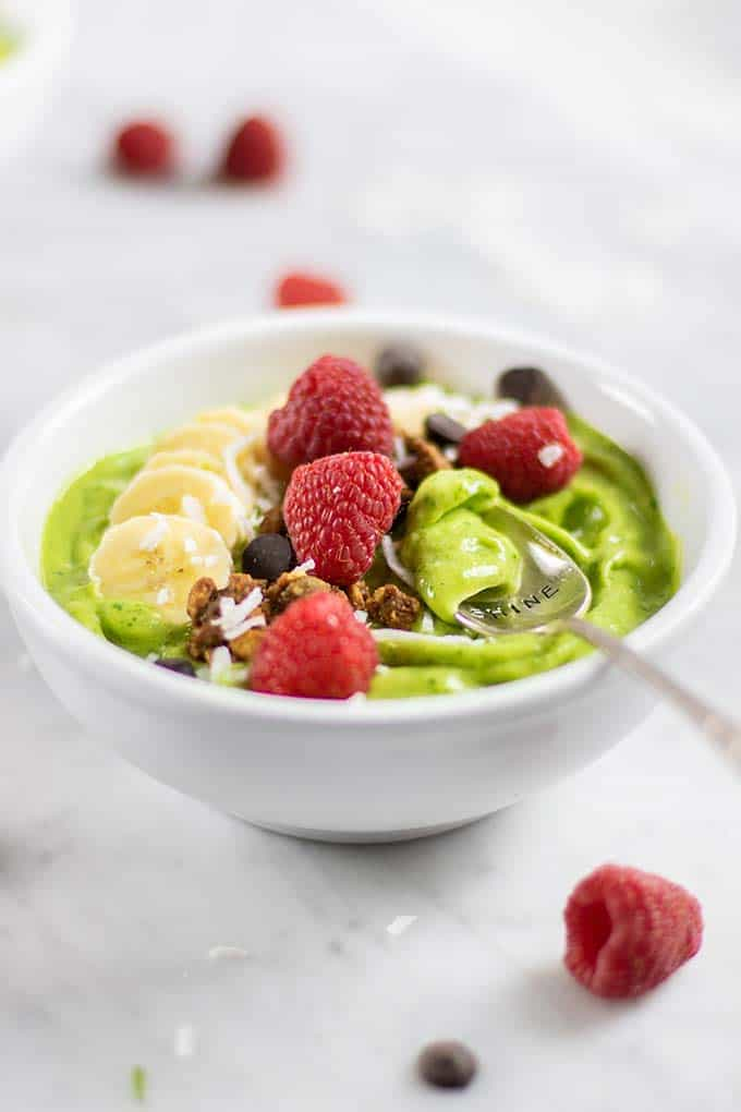 A bowl surrounded by raspberries filled with this healthy green smoothie bowl recipe.