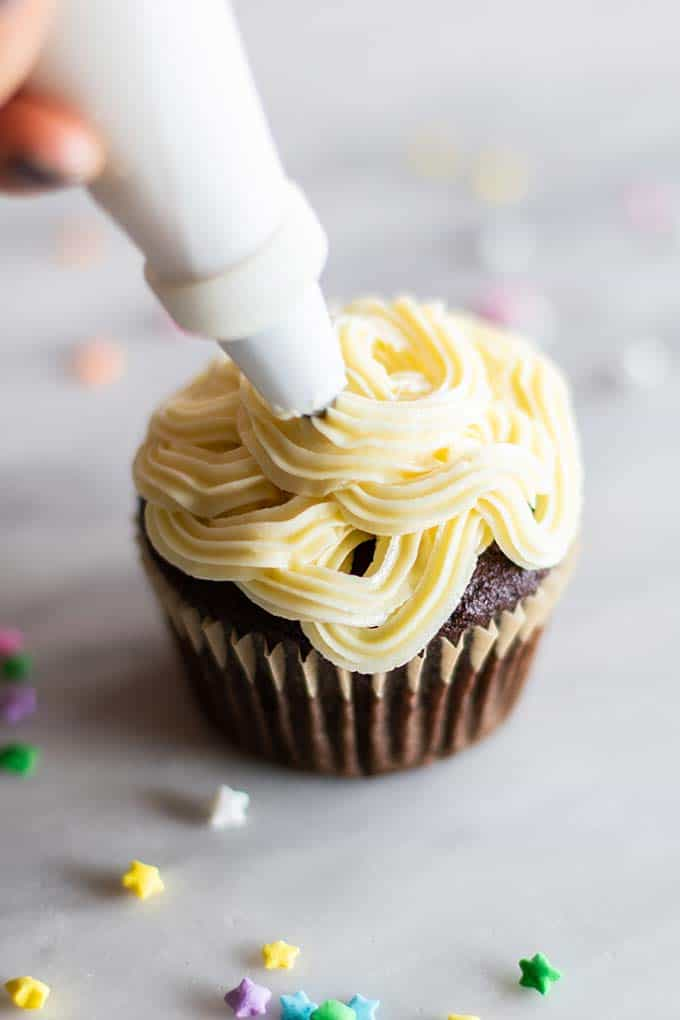 Healthy White Chocolate Buttercream Frosting being piped onto a chocolate cupcake.