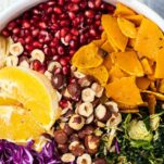 A close up look at a salad bowl filled with red cabbage, oranges, pomegranate, butternut squash, and hazelnuts.