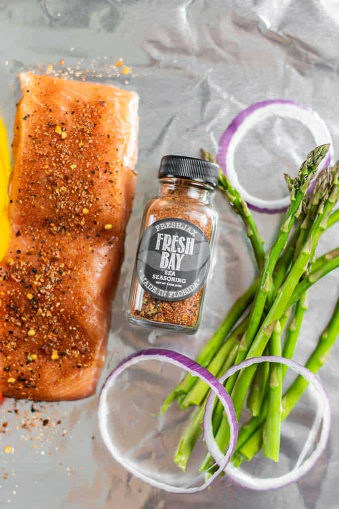 A foil packet with salmon and asparagus.