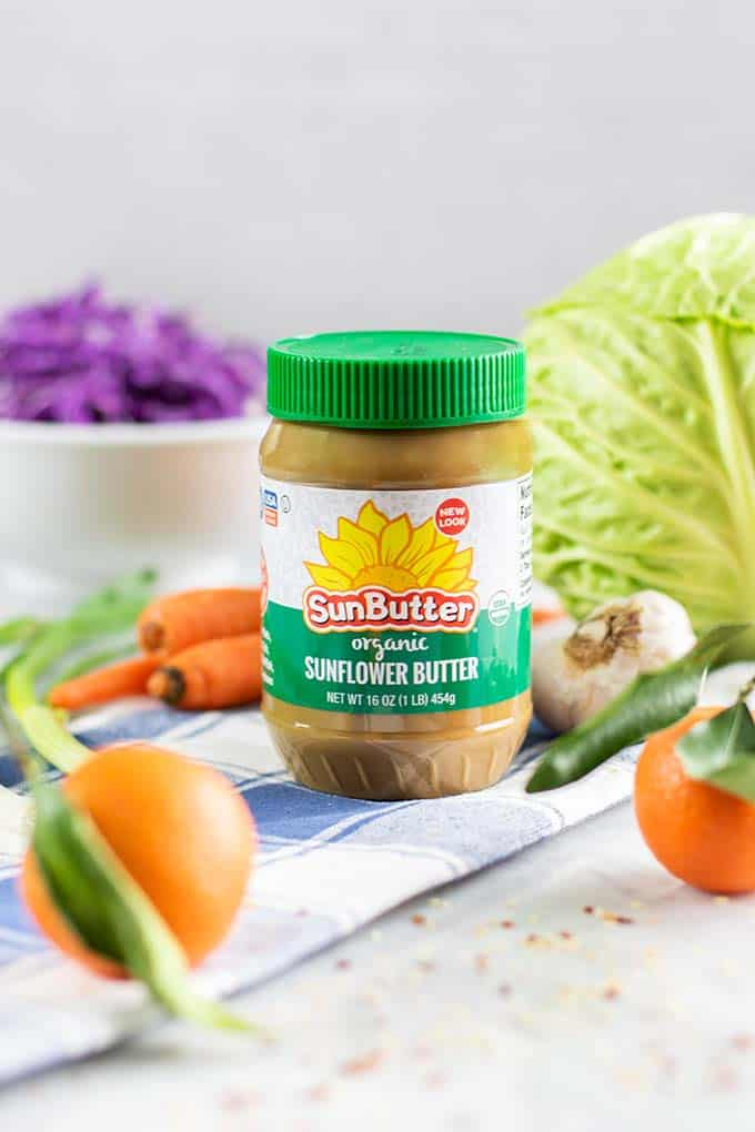 A jar of Sunbutter with the ingredients for this salad.