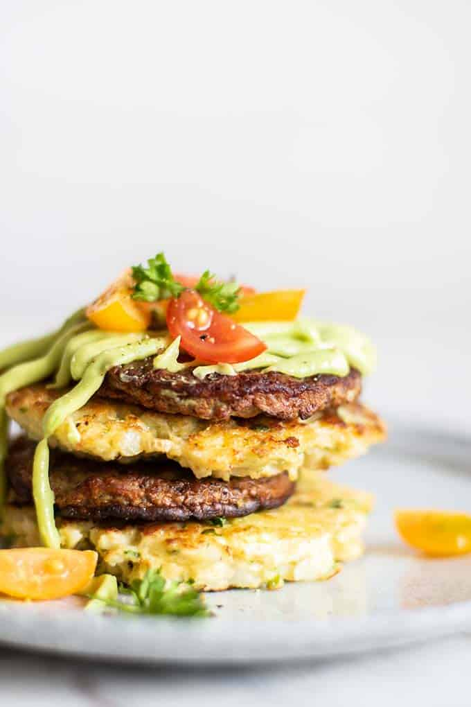 A close up view of perfectly browned cauliflower fritters and sausage, drizzled with avocado sauce.
