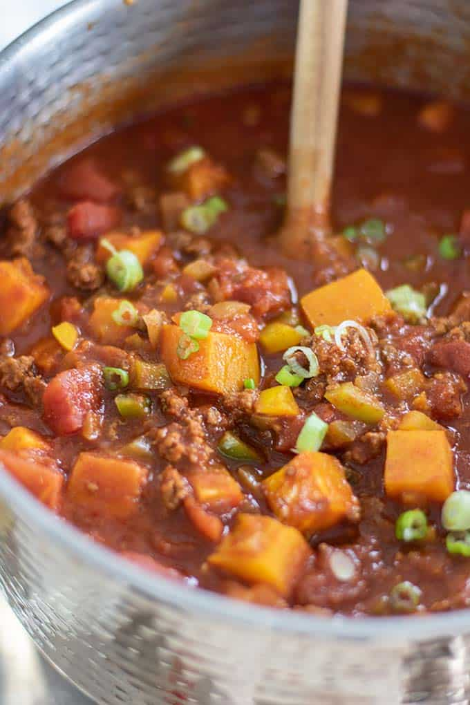 A pot of chili with beef, butternut squash, and peppers.