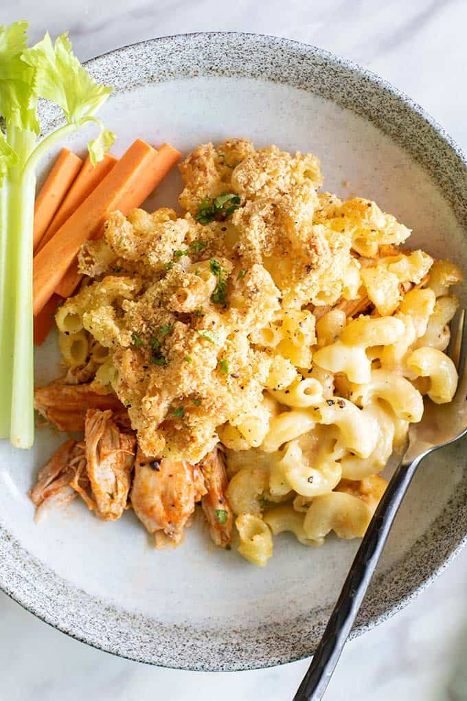 A close up view of a baked buffalo chicken mac and cheese served with carrots and celery.