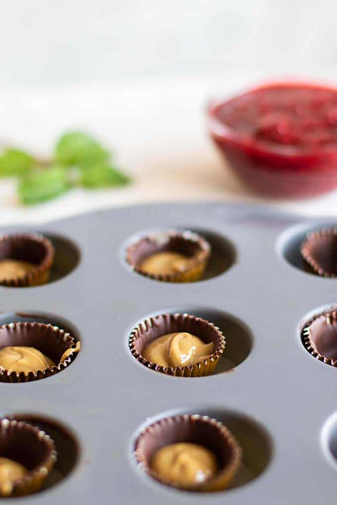 Foil wrappers being lined with chocolate and filled with a creamy Sunbutter.