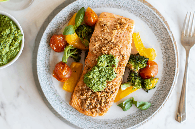 Pesto salmon served with tomatoes, peppers and broccoli.