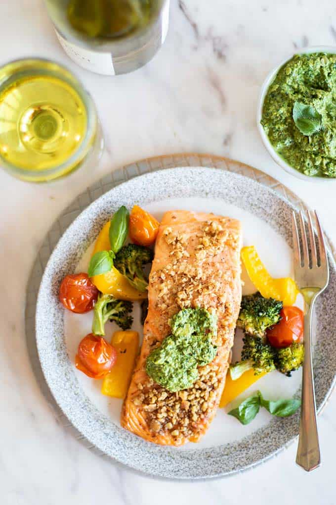 A plate of pesto salmon and veggies served with a glass of white wine.