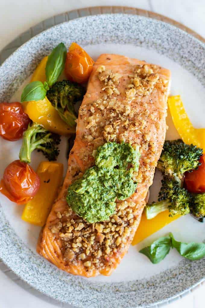 A close up shot of pesto salmon coated in walnuts served with veggies.