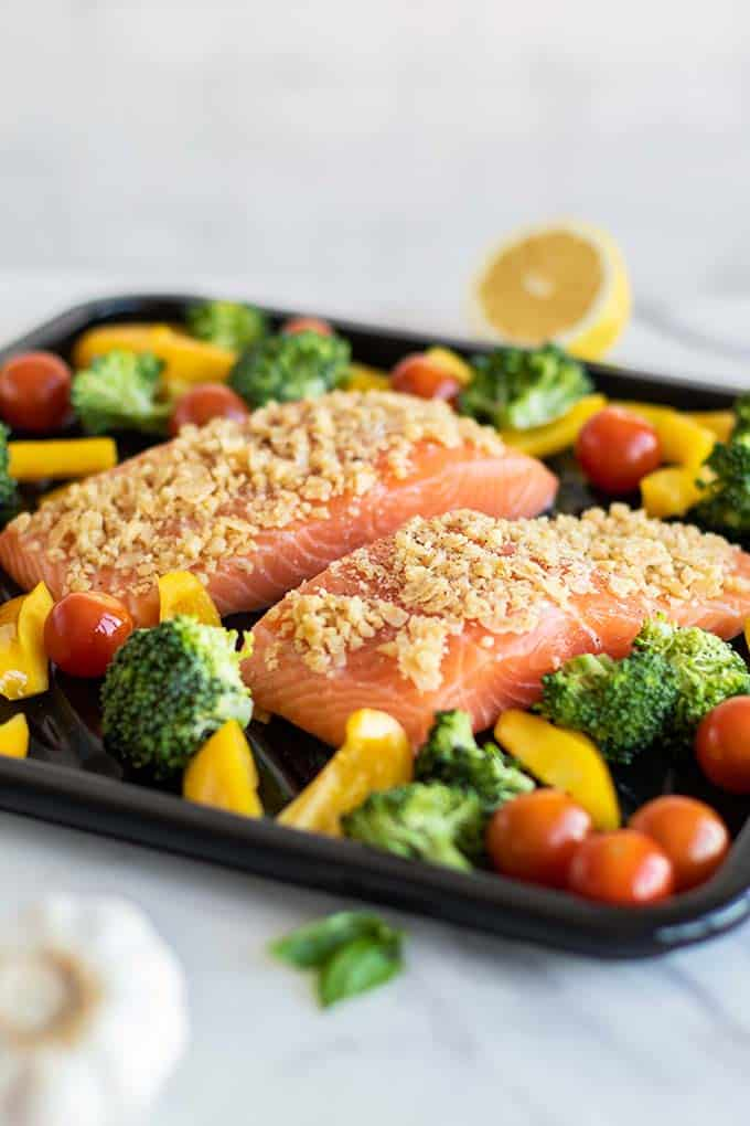 A baking sheet with 2 pieces of salmon and veggies.