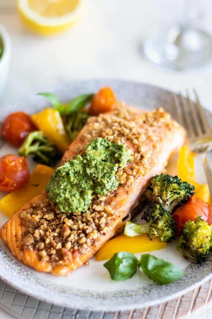 A piece of pesto salmon coating in walnut and served with vegetables.