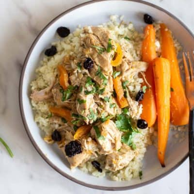 A plate with a serving of crockpot moroccan chicken, carrots, and cauliflower rice.