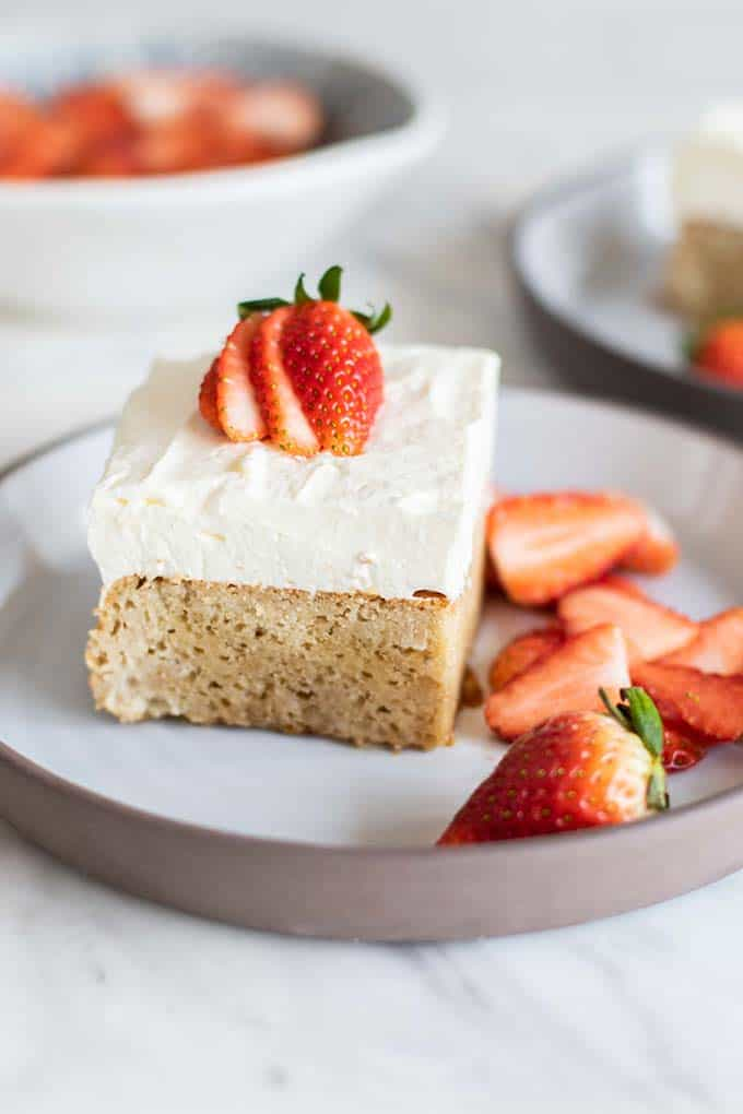 A healthy tres leches cake topped with coconut whipped cream.