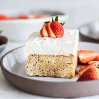 A slice of almond flour gluten free tres leches cake with strawberry slices.