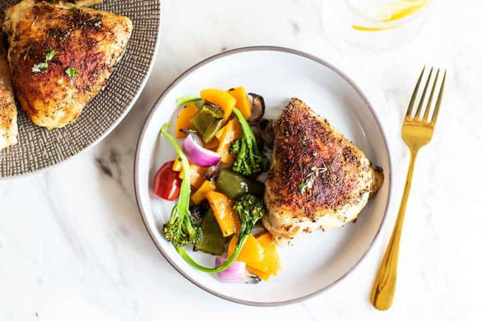 A plate with a baked chicken thigh and a serving of roasted vegetables.
