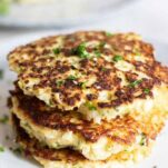 A stack of 3 cauliflower patties fried golden.
