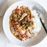 Easy crockpot gumbo recipe shown served over rice on a plate.