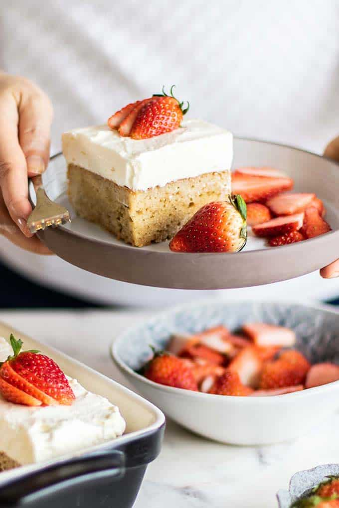 Michelle holding a plate with a slice of tres leches cake with strawberries.