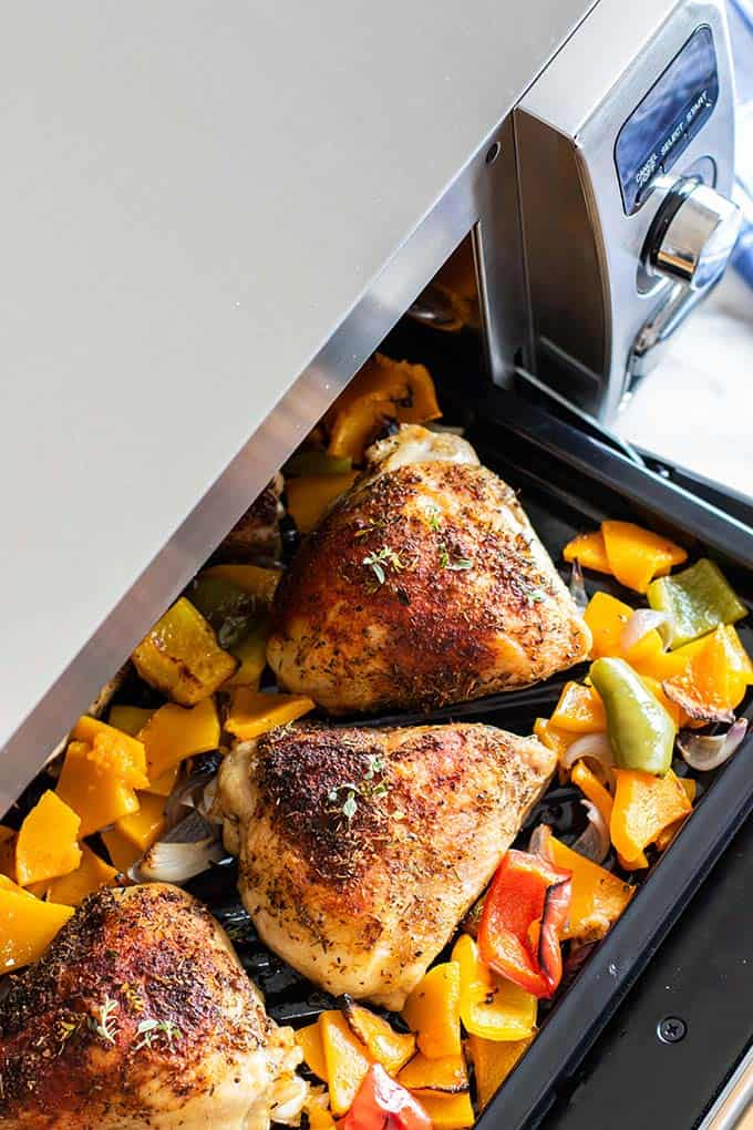 Baked chicken thighs and veggies coming out of the oven.