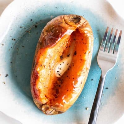 A soft baked sweet potato topped with butter and pepper.