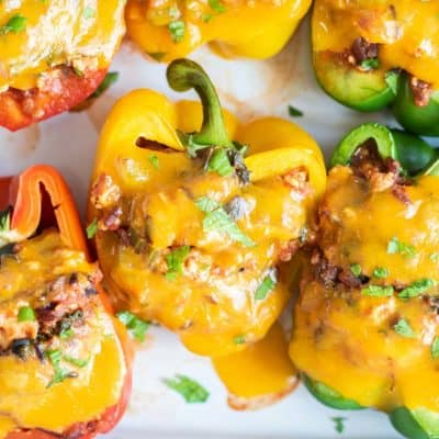 Cheesy stuffed bell peppers in a baking dish.
